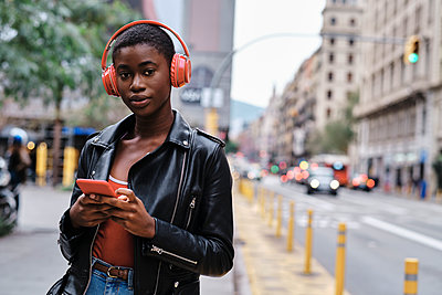 Woman wearing headphones and jacket using smart phone while standing in city - p300m2250157 by Alvaro Gonzalez