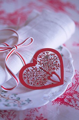 Christmas place setting with red heart and ribbon - p3490553 by Jan Baldwin