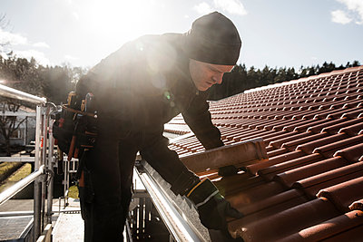 Male worker repairing roof of building at construction site on sunny day - p426m2101397 by Katja Kircher