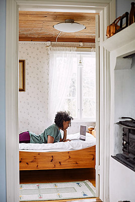 Side view of young woman using laptop while lying on bed seen through doorway at home - p426m2117151 by Maskot