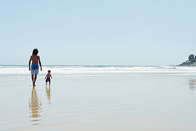 Father and son walking on beach - p429m2022978 by Lindsay Upson