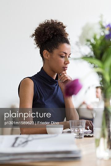 Junge Geschäftsfrau mit Afro vor Laptop - p1301m1589623 von Delia Baum