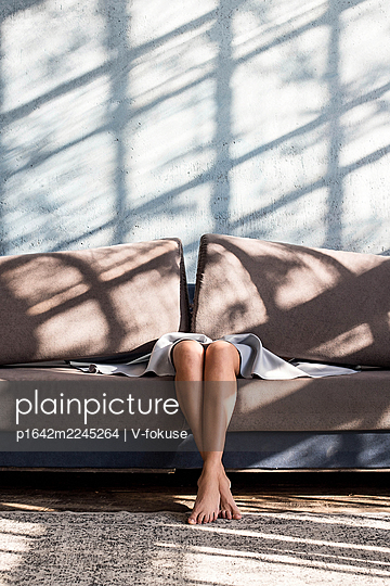 Legs and feet of a woman sitting on the couch - p1642m2245264 by V-fokuse