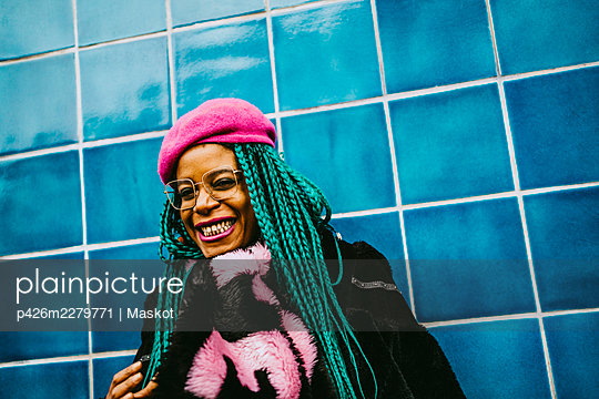 Portrait of cheerful mid adult woman standing against blue tiled wall - p426m2279771 by Maskot