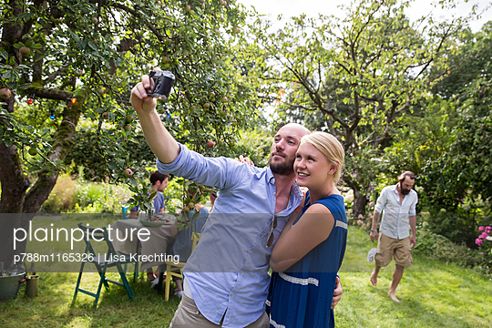 Junges Paar macht ein Selfie im Garten - p788m1165326 von Lisa Krechting