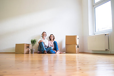Smiling mature couple sitting on floor in empty room next to cardboard boxes - p300m1562986 by Robijn Page