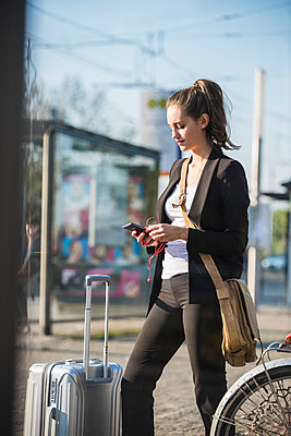 Young woman with luggage at tram station in the city checking cell phone - p300m2059409 von Uwe Umstätter