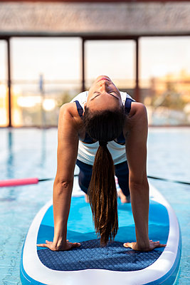 Female yoga instructor in bridge position on paddleboard over swimming pool - p300m2240854 by Jose Carlos Ichiro