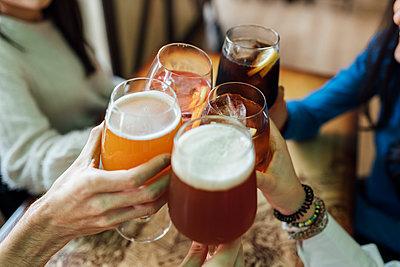 Friends hands toasting wineglasses over table at bar - p300m2243039 by Ezequiel Giménez
