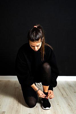Brunette fitness concept in studio against black wall - p300m2281860 von Giorgio Fochesato