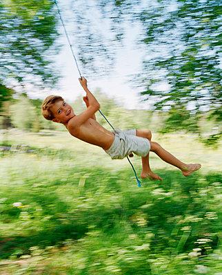 A boy swinging in a green garden - p31222289f by Per Eriksson