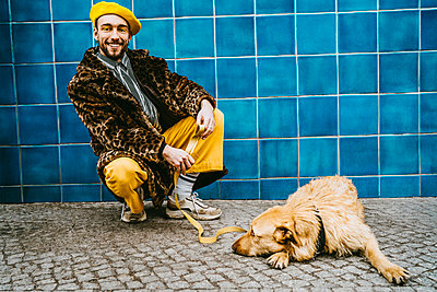 Full length of young man crouching by dog lying on footpath against blue tiled wall - p426m2279716 by Maskot