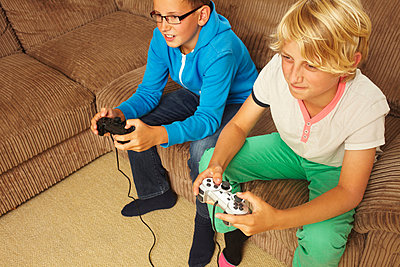 Two boys playing video game - p924m744550f by Emma Kim