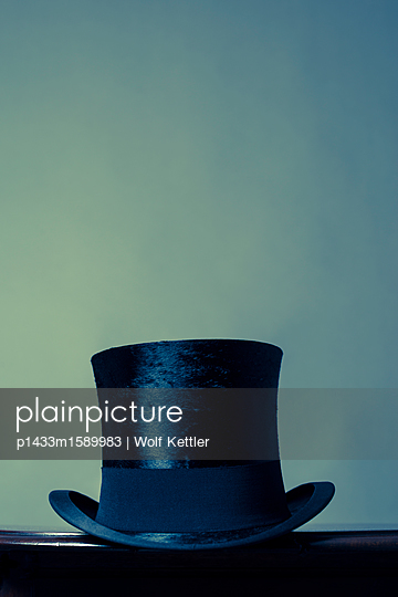 Black top hat on dark brown surface before pale blue background. - p1433m1589983 by Wolf Kettler