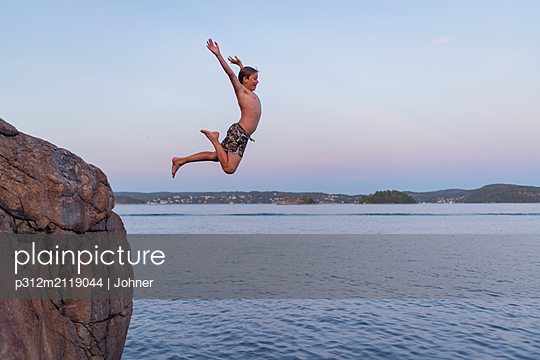 Boy jumping into sea - p312m2119044 by Johner