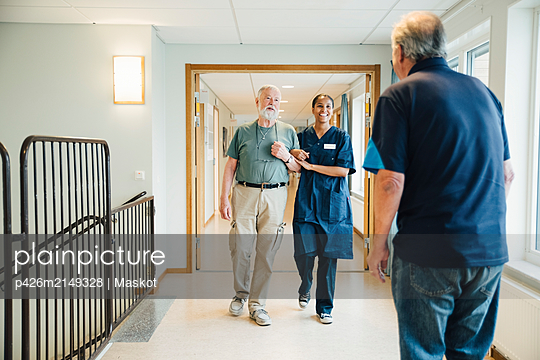 Senior man walking arm in arm with female nurse while looking at friend standing in alley at nursing home - p426m2149328 by Maskot