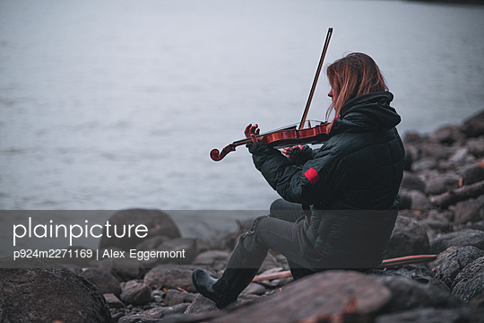 Woman playing violin by Lillooet Lake, British Columbia, Canada - p924m2271169 by Alex Eggermont