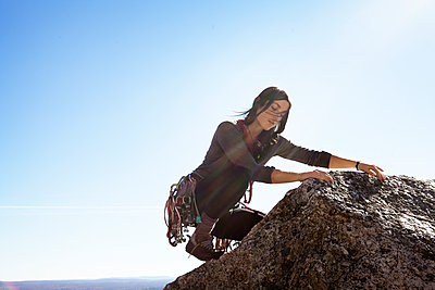 Woman rock climbing against sky on sunny day - p1166m1231468 by Cavan Images