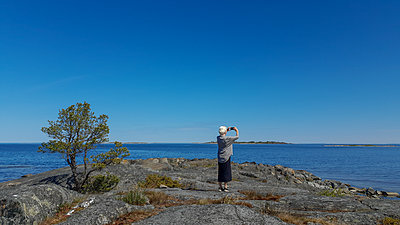 Elderly woman taking photo by the sea - p1418m2187100 by Jan Håkan Dahlström