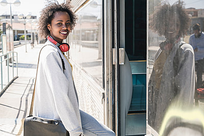 Portrait of a smiling young woman entering a train - p300m2155845 by Uwe Umstätter