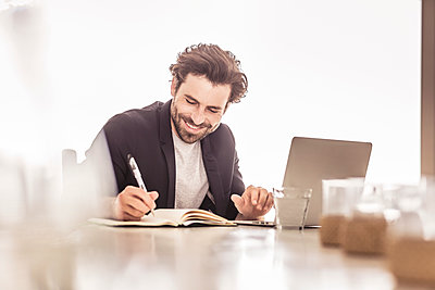 Young man in business jacket working on a laptop and taking notes in a beach house - p300m2167497 by Floco Images