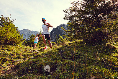 Young couple trail running in mountain scenery - p913m1113039 by LPF
