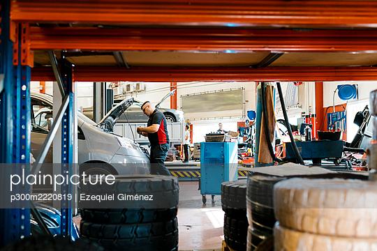 Mechanic repairing car in auto repair shop - p300m2220819 by Ezequiel Giménez