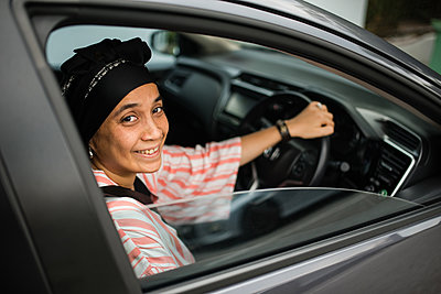 Asian woman driving car - p1166m2131287 by Cavan Images