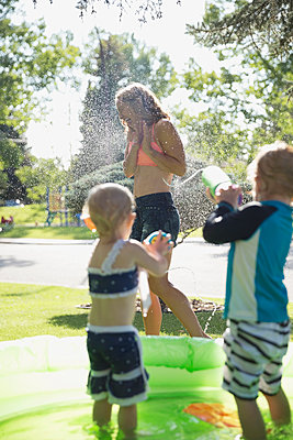 Daughter and son spraying mother with squirt guns in sunny wading pool - p1192m1184005 by Hero Images