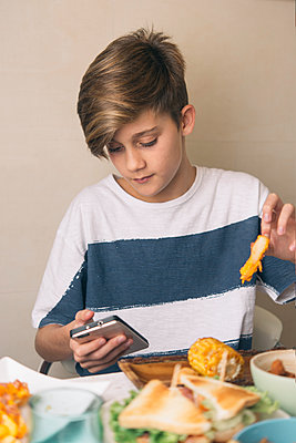 Boy eating at dining table and looking at the phone at the same time - p300m1581416 von skabarcat
