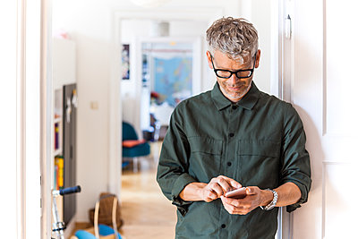 Mature man leaning against door case at home using cell phone - p300m2030526 by Tom Chance