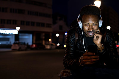 Man in the city at night with smartphone and headphones - p300m2167023 by Rafa Cortés