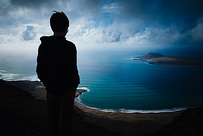 Boy looking at scenic ocean bay view with storm clouds overhead, Lanzarote, Canary Islands, Spain - p301m2075844 by Sven Hagolani