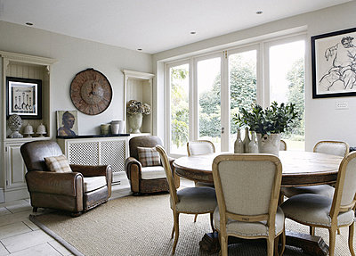 Matching brown leather chairs and vintage clock in dining room of Guildford home - p349m790395 by Brent Darby