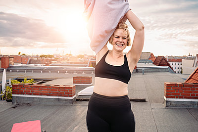 Portrait of smiling woman removing t-shirt on rooftop against dramatic sky - p426m2233619 by Maskot