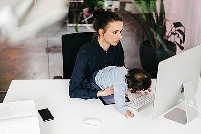 Junge Geschäftsfrau mit Tochter im Büro - p586m1451947 von Kniel Synnatzschke