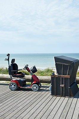 Mobility scooter next to wicker beach chair - p851m1116267 by Lohfink