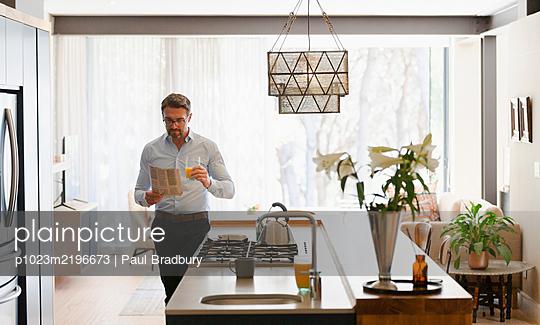 Businessman reading newspaper in morning kitchen - p1023m2196673 by Paul Bradbury