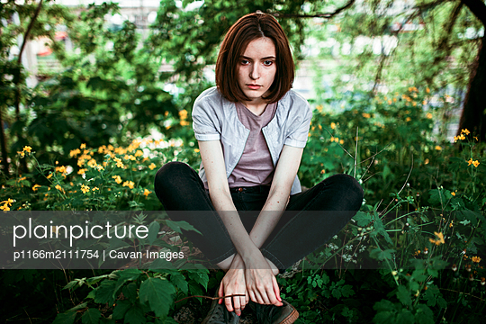 A woman is sitting on a stone in a grove - p1166m2111754 by Cavan Images