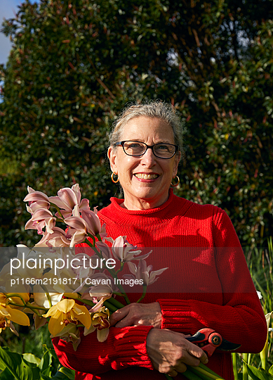 Older Woman Holding Bouquet of Fresh cut flowers in her Garden - p1166m2191817 by Cavan Images