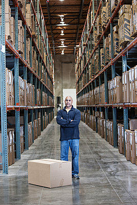 A black warehouse worker standing near boxed products in a distribution warehouse. - p1100m2002275 by Mint Images