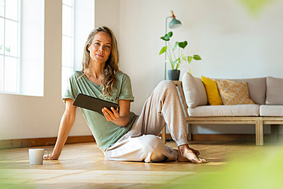 Woman in loungewear holding digital tablet while sitting on hardwood floor at home - p300m2277504 by Steve Brookland