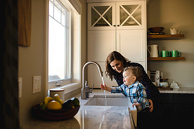 Mother helping toddler son wash hands at kitchen sink - p429m1418413 by Erin Lester