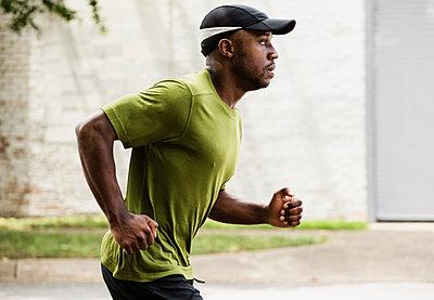 Black man running on city street - p555m1420914 by Roberto Westbrook