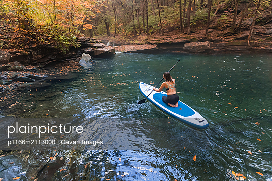 Woman paddle boarding in a fall scene on a clear river - p1166m2113000 by Cavan Images