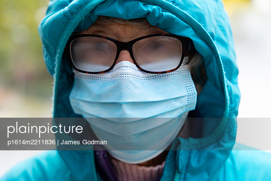 Woman in mask wearing fogged up glasses - p1614m2211836 by James Godman