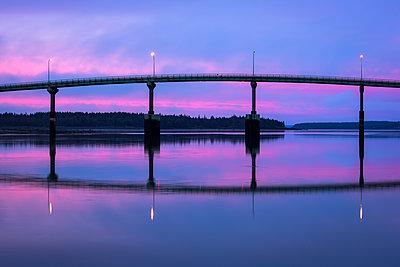 Dramatic pink sky at sunrise behind bridge to Campobello Island - p1166m2136521 by Cavan Images