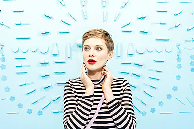 Woman in front of light blue background with beauty cosmetic articles  - p1332m2055050 by Tamboly