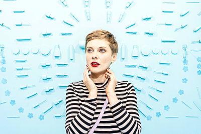 Frau vor hellblauem Hintergrund mit Kosmetikprodukten - p1332m2055050 von Tamboly