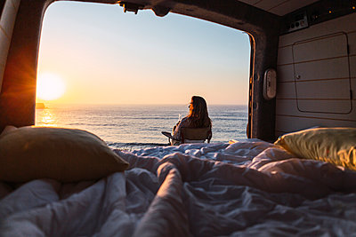 Woman admiring sunset view while while sitting on chair by camper van at beach - p300m2220572 by Alexandra C. Ribeiro